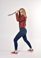 Full length portrait of a pretty blonde girl wearing red leather jacket denim jeans and sneakers. Standing pose, holding a dagger,  on a studio background.
