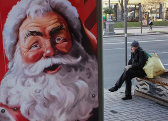 Man waits for a bus at a stop of public transport, decorated with an image of Santa Claus, in central Kiev