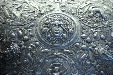 Saint Petersburg, Russia - June 14, 2016: Close-up of pageant shield with engraved Medusa surrounded by fantastic beasts