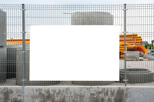 Blank white banner mockup on the fence of construction site