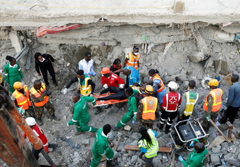 An injured women rescued from the rubble is carried by rescuers at the scene where a building collapsed in Nairobi