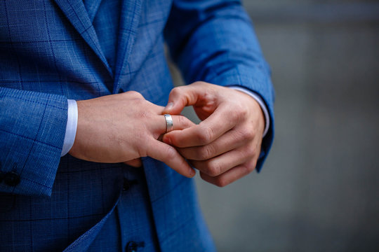 Groom in a suit holding ring