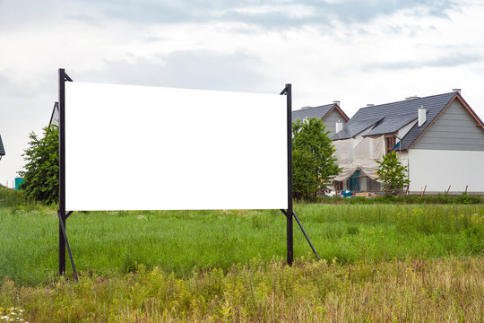 Blank white billboard mockup in the front of house under construction in the suburbs