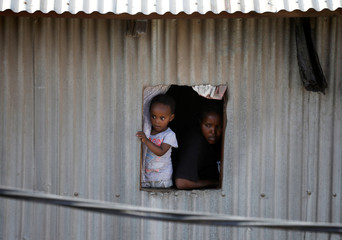 People look out of a window as they observe rescue efforts at the scene where a building collapsed in Nairobi