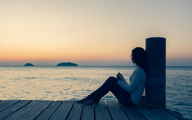 beautiful Lonely woman sitting on a wooden bridge sunset.are Lonely.Single women sat with stress