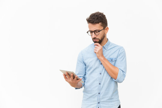 Sad frowning guy with tablet reading content on screen. Handsome young man in casual shirt and glasses standing isolated over white background. Wireless internet concept