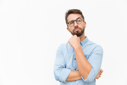 Pensive male customer looking away at copy space, touching chin, thinking. Handsome young man in casual shirt and glasses standing isolated over white background. Advertising concept