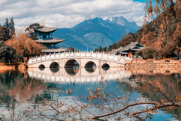 Foto auf Acrylglas Cappuccino Beautiful view of the Jade Dragon Snow Mountain and the Suocui Bridge over the Black Dragon Pool in the Jade Spring Park, Lijiang,