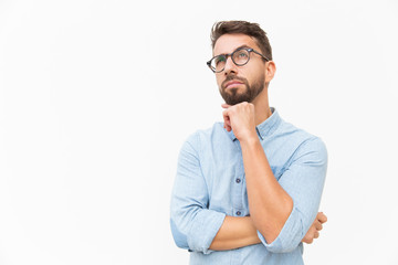 Fototapeta Pensive customer thinking over special offer, touching chin, looking up. Handsome young man in casual shirt and glasses standing isolated over white background. Advertising concept obraz
