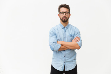 Successful confident male entrepreneur posing with arms folded. Handsome young man in casual shirt and glasses standing isolated over white background. Confident man concept