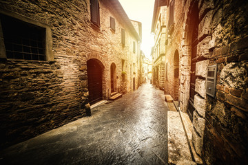 Fotobehang Oude gebouw Narrow street in an old village in Tuscany at sunset