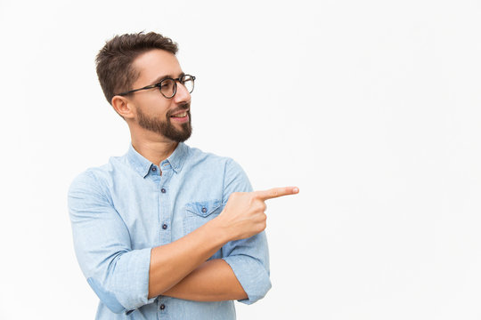 Positive male customer presenting new product, pointing finger at copy space. Handsome young man in casual shirt and glasses standing isolated over white background. Presentation concept
