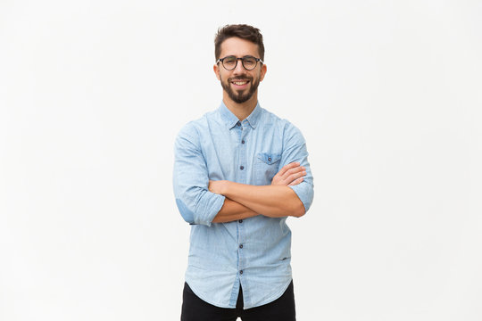Happy laughing guy posing with arms folded. Handsome young man in casual shirt and glasses standing isolated over white background. Male portrait concept
