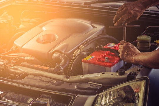 Car service ,fitting a car battery with wrench . soft focus picture