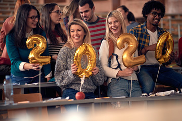 happy students celebrating 2020 new year toghether in university