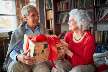 Elder couple exchanging Christmas gifts