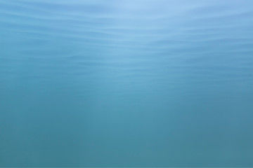 Picture of blue to green shades of water mass from under water. Fine structure of waves from below. Light blue to azure color transition.