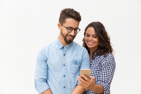 Happy cheerful woman showing message on phone to her boyfriend. Young woman in casual and man in glasses in glasses posing isolated over white background. Good news concept