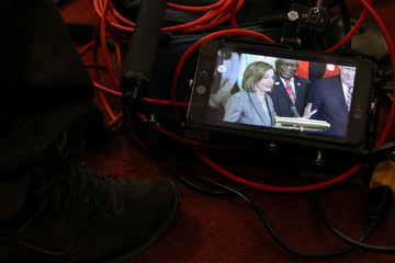 U.S. House Speaker Nancy Pelosi (D-CA) is seen on a monitor at the feet of a cameraman during a news conference on Capitol Hill in Washington