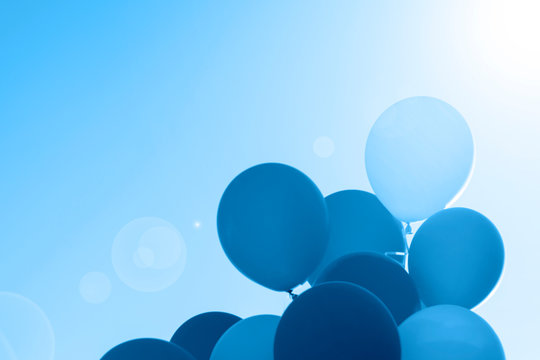 Color of 2020 year, classic blue. Group of balloons with helium on the sky background. Trend color.