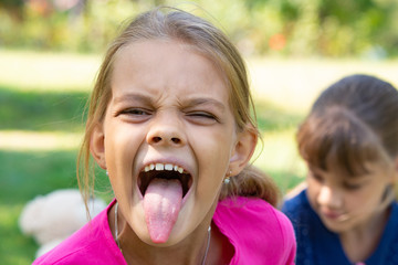 The girl turned and funny shows a long tongue