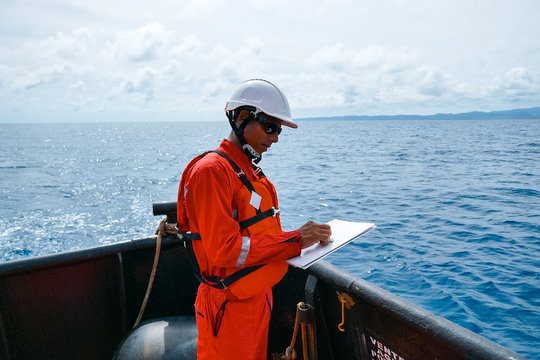 Safety officer, standing on an industrial ship, wearing overalls, a helmet, safety goggles and holding a clipboard with checklists.