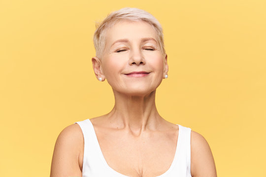 Fashionable beautiful retired Caucasian woman with pixie hairdo wearing casual clothes posing in studio keeping eyes closed and smiling with pleasure and enjoyment, listening to good music or dreaming