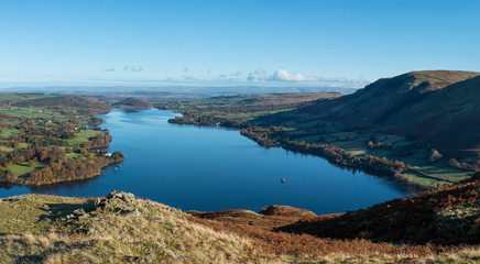 Aluminium Prints Blue Beautiful Autumn Fall landscape of Ullswater and surrounding mountains and hills viewed from Hallin Fell on a crisp cold morning with majestic sunlgiht on the hillsides
