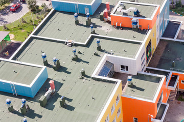 Top view flat roof with air conditioners and hydro insulation membranes on top of a modern blue and orange apartment building sunny summer day. Wall mural