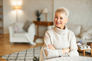 People, lifestyle and mature age concept. Indoor shot of middle aged short haired woman sitting in...