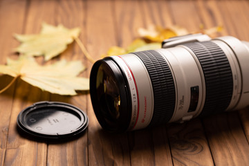 camera lens on wood background with autumn fall leaves