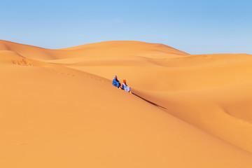 Two girls in headscarves in the Sahara desert.