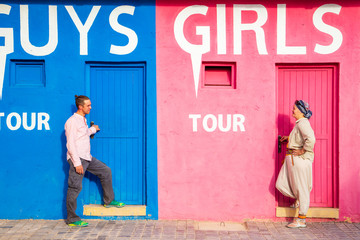 Guy with a girl near an unusual funny wall. The concept of gender differences.