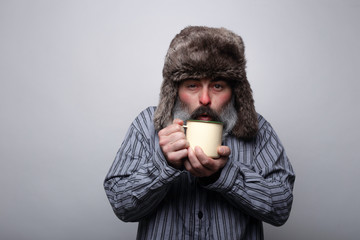 Sick man with pajamas and with a cap blowing a cup of hot tea on a gray background