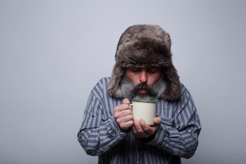 Flu sick man with pajamas and with a cap blowing a cup of hot tea on a gray background. Health concept.