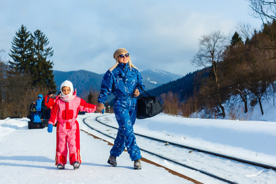 mother and daughter are wearing ski suits near the railway