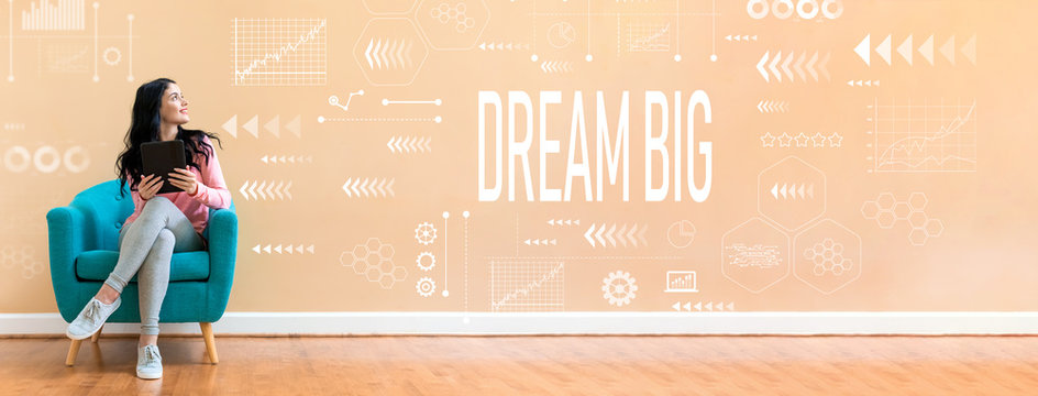 Dream big with young woman holding a tablet computer in a chair