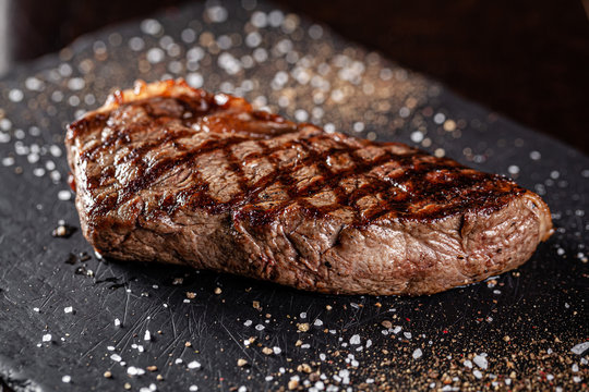 Farm organic food concept. Grilled beef steak with grill. Fried steak on on black slate, on a black background.