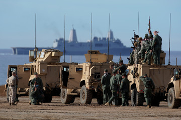 """U.S. Marines role playing as enemy combatants pose for a team picture after a training exercise involving the an amphibious landing by the 1st Marine Division's during  """"Exercise Steel Knight"""" at Camp Pendleton, California"""