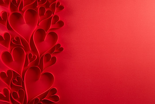 Red paper hearts on red paper background. Love and Valentine's day concept.