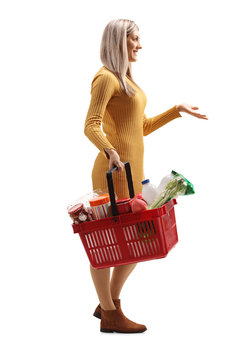 Young woman carrying a full shopping basket and gesturing with hand