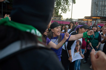 Women react during a demonstration against gender violence, in Mexico City