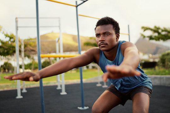 Athletic young man in sportswear doing physical exercises at outdoor gym park - young african american man doing squats