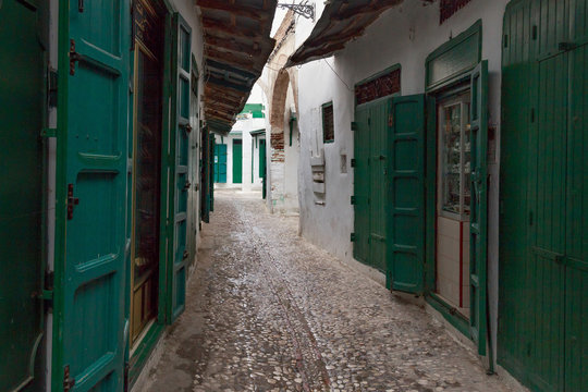 Green wooden doors of the old stores in Tetouan Medina quarter in Northern Morocco. A medina is typically walled, with many narrow and maze-like streets.