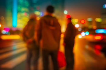 Abstract background of People across the crosswalk at night in Shanghai, China.