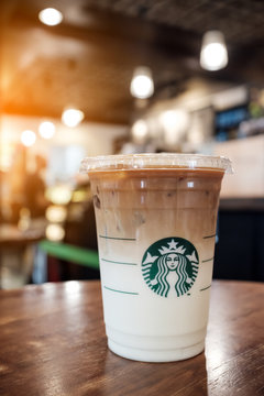 BANGKOK, THAILAND - JULY 7, 2017_Starbucks iced beverage coffee cup with logo, favorite iced caramel macchiato coffee, image captured in the shop with beautiful bokeh and sunlight effect