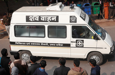A hospital vehicle carries the body of a rape victim to her residence in New Delhi