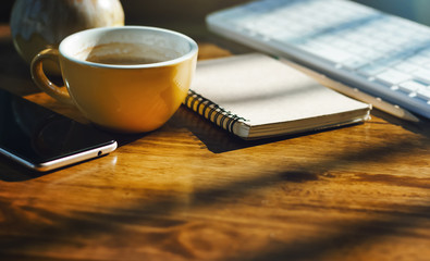 Place of work on wooden desk with cup of coffee, notebook, mobile phone and computer keyboard. Background vintage tone