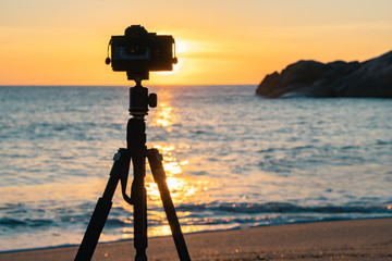 Camera standing on a tripod on the beach against the background of dawn