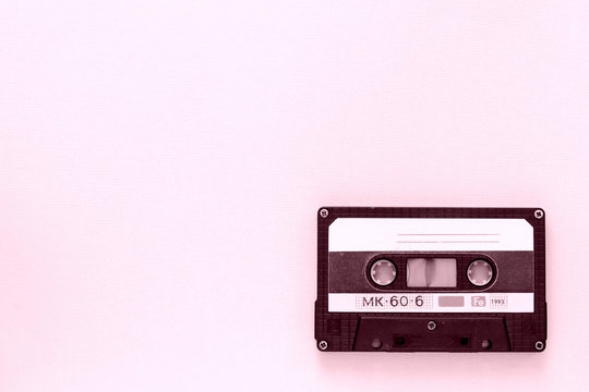 Old audio tape cassette close-up. Old technology concept. Pink color toned
